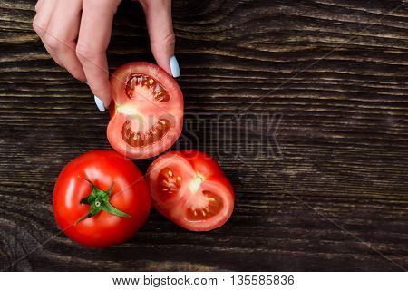 The girl in the hands holding a tomato on a wooden background