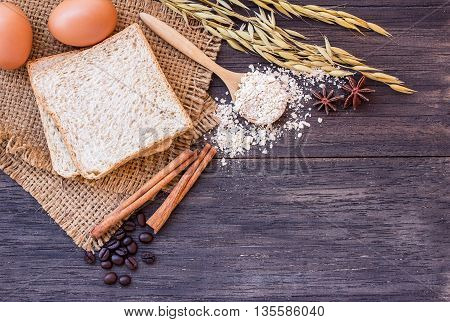 Ears of wheat and egg with slice of bread on a dark wooden table background