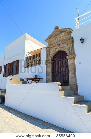 Beautiful large wooden door, surrounded by marble and a typical house on island of Lindos.