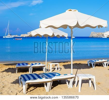Beach with sunshades and sunbeds against the backdrop of the picturesque bay of blue sea and mountains
