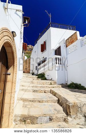 Beautiful large wooden door, surrounded by marble and a typical house on the island of Lindos.