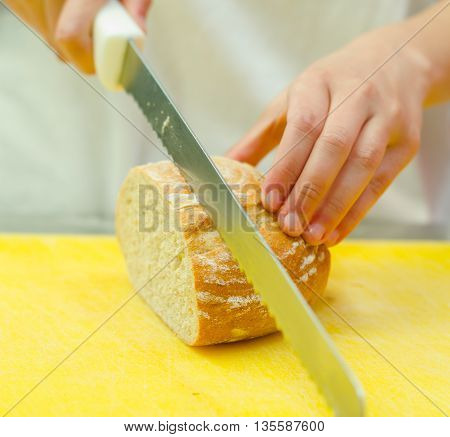 Cutting slices from loaf of bread sitting on yellow surface, hand holding large knife.