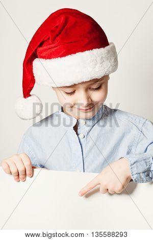 Little Boy Wearing Santa Hat Point the Finger at White Banner