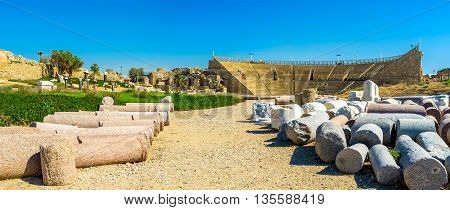 The ancient Roman Colosseum with the lying ruined columns on the foreground Caesarea Israel.