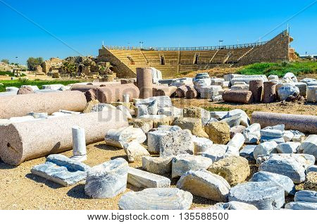 The preserved and restored part of the ancient Colosseum surrounded by the artifacts and ruined buildings Caesarea Israel.