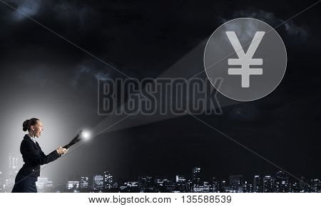 Young elegant businesswoman with flashlight in darkness and yen currency symbol