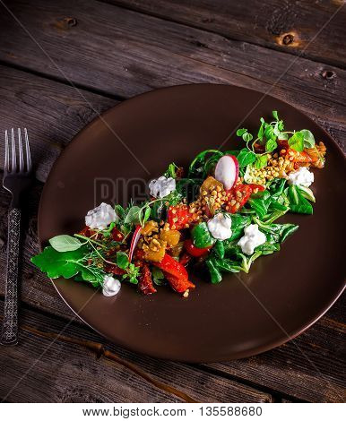 Salad With Goat Cheese,greens And Grilled Pepper On Brown Plate.