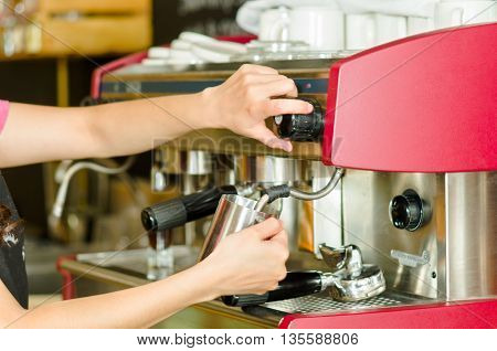 Female hands working operating industrial coffee maker, steaming milk in metal container.