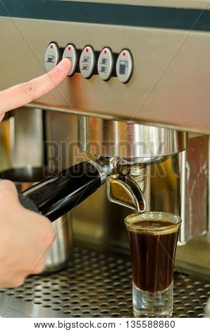 Female hands working operating industrial coffee maker, pouring espresso shot.