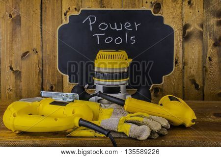 power tools and work gloves in front of chalkboard reading power tools on wood background