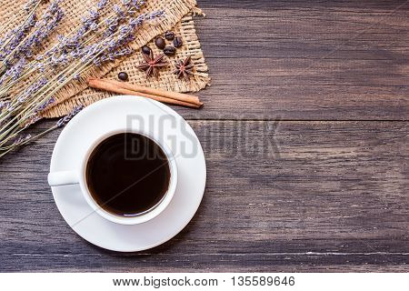 Cup of coffee and lavender flower on dark wooden table background with copy space