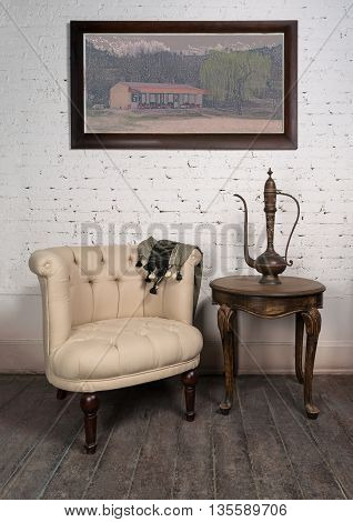 Vintage still life of old beige armchair brass teapot framed painting and small antique table on dark brown wooden floor and white bricks wall in Studio