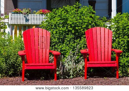 Two red Adirondack chairs in the summer sun.