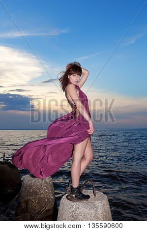 brunette in maroon dress on bank of river against evening sky