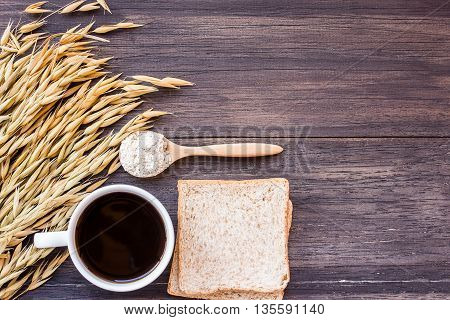 Ears of wheat and coffee with slice of bread on a dark wooden table background.top view with copy space