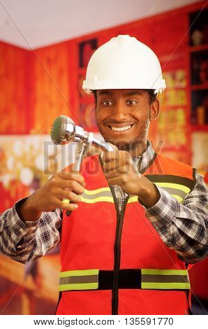 Young engineer wearing square pattern flanel shirt with red safety vest, holding showerhead and pliars smiling to camera.