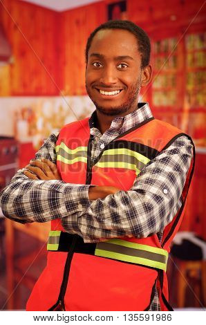 Young carpenter worker wearing square pattern flanel shirt and red safety vest, posing with arms crossed, smiling to camera.