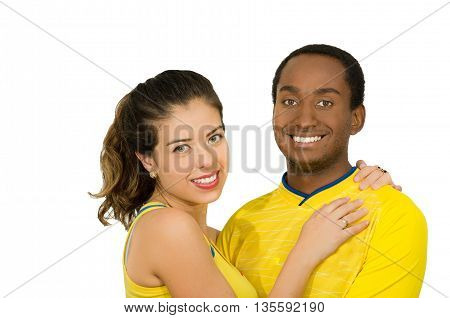 Charming interracial couple wearing yellow football shirts, embracing friendly while posing for camera, white studio background.