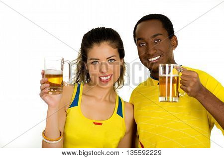 Charming interracial couple wearing yellow football shirts, posing for camera holding beer glasses and smiling, white studio background.