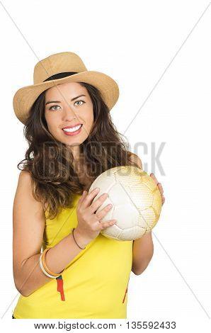 Hispanic brunette wearing yellow football shirt and hat, posing for camera while holding ball, white studio background.