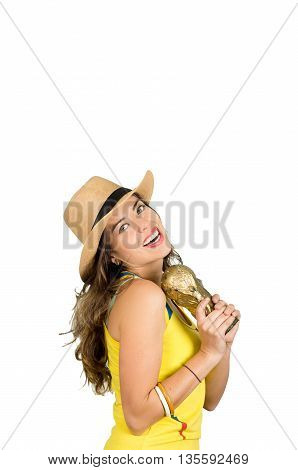 Hispanic brunette wearing yellow football shirt and hat, posing for camera while holding trophy, white studio background.