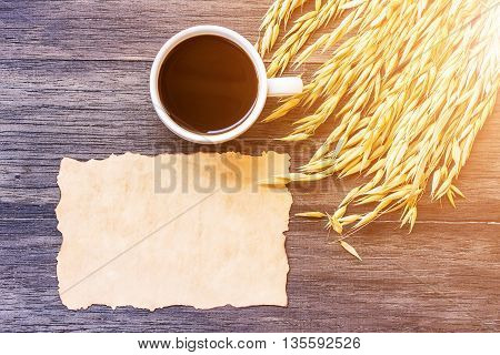 Ears of wheat and old paper with cup of coffee on dark wooden table background. top view with copy space