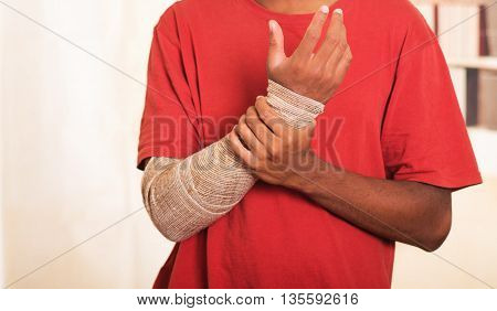 Closeup man in red shirt wearing large grey bandage over lower right arm, supporting with other hand.
