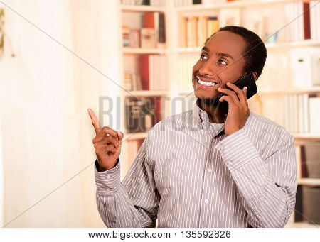 Handsome man wearing casual clothes talking on mobile phone while pointing upwards, white bookshelves background.