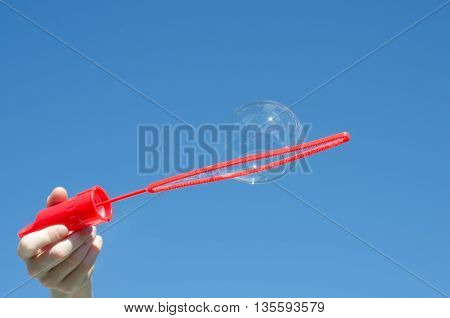 Blowing bubbles on a sunny day against blue sky