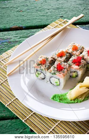 Rolls Decorated With Caviar On White Plate And Chopsticks. Old Green Wooden Background.