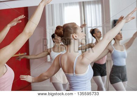 Ballerinas With Arms Raised Dancing In Studio