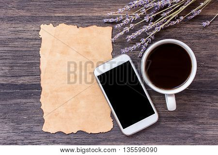 Old paper smart phone and cup of coffee with lavender flower on dark wooden table background. top view with copy space