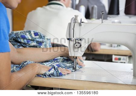 Tailor Using Sewing Machine At Workbench