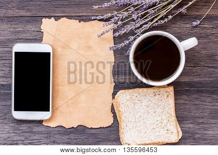 Old paper smart phoneslice of bread and cup of coffee with lavender flower on dark wooden table background. top view with copy space