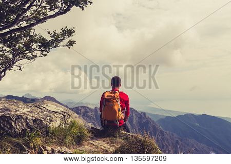 Hiking man climber or trail runner looking at inspirational mountains landscape view. Fitness and healthy lifestyle outdoors in summer nature. Accomplished climber or traveller.