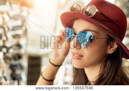 Happy woman buying sunglasses in shop on the street