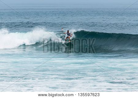 BALI INDONESIA - MARCH 29 2016: Young surfers in rough seas sail on Blue Ocean Wave on Balangan beach Bali