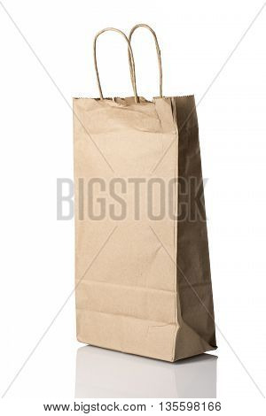 A brown paper bag possibly for alcohol angled and isolated on white with reflection.