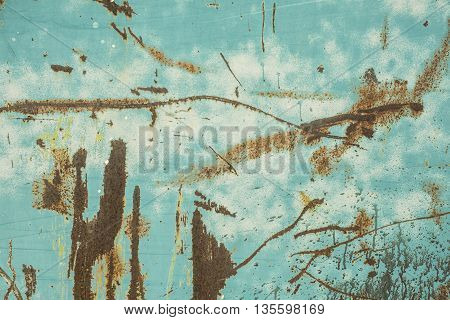 An old grungy turquoise metal surface with rust spots scratches and paint splatter.