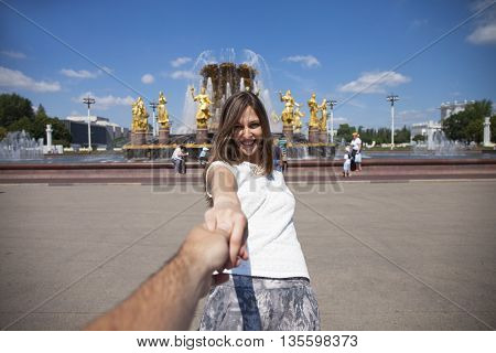 Follow me. Young happy woman pulls the guys hand on the Fountain of friendship of the people daily view at VDNH exhibition in Moscow, Russia.