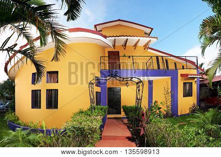 Yellow house with interesting design in summer time