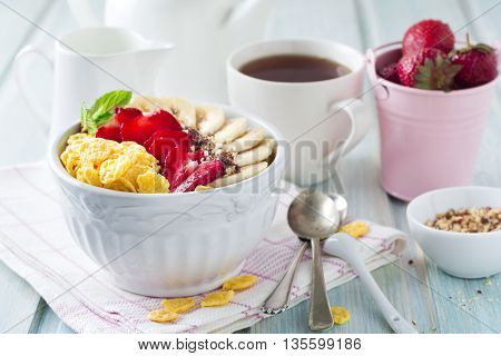 Healthy breakfast. Corn flakes, banana, strawberry, almond, chocolate and yoghurt in a ceramic bowl on a light background.