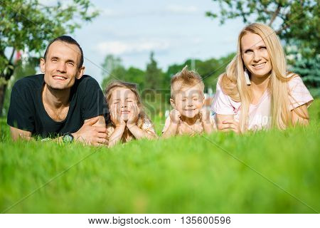 Portrait of happy parents and kids lying at the park