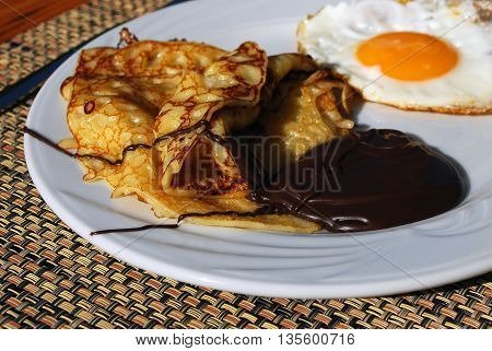 Pancake with Chocolate and Egg on White Plate on the Table