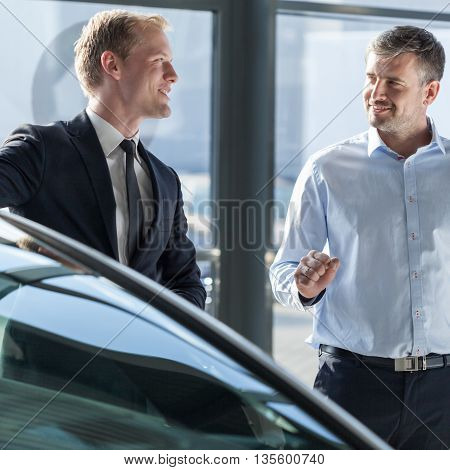 Car dealer showing vehicle to business client