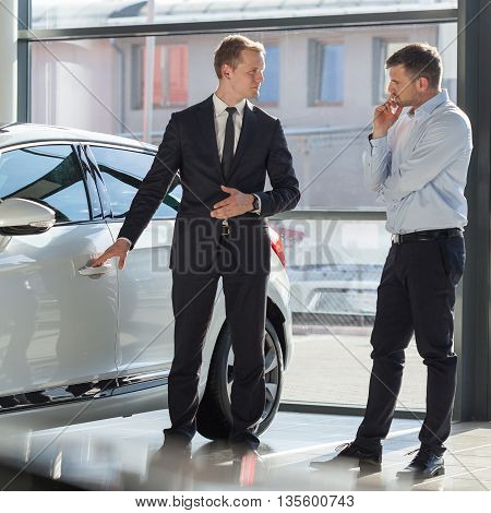 Car agent and interested customer at store