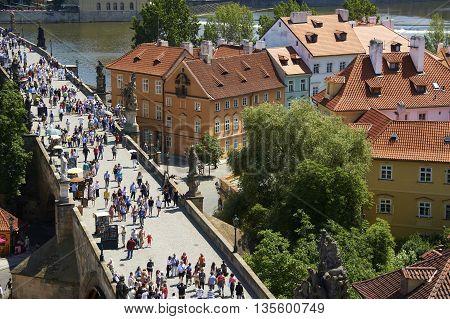 PRAGUE, CZECH REPUBLIC - SUMMER 2014 : Pedestrians and vendors (tourists) on the Charles Bridge, Vltava river