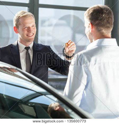 Salesman giving car key for car test