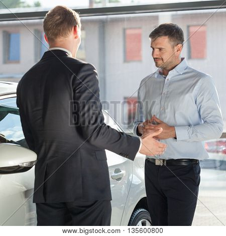 Auto seller discussing with client about car