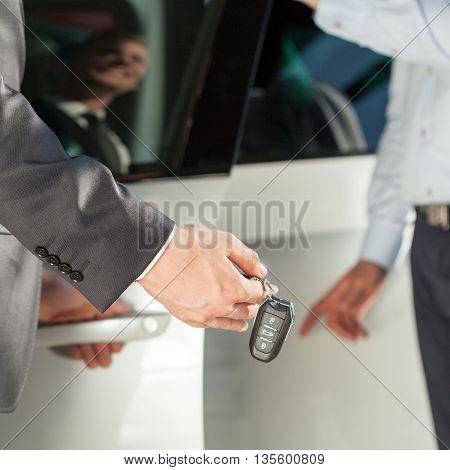 Car dealer giving car keys to client